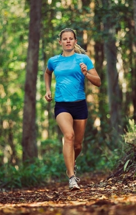 Female runner jogging on a wooded trail in the summer time.