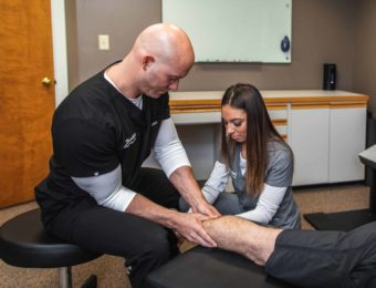 Chiropractor Dr. Brian A. Zelasko And His Assistant Treating Male Patient's Calf Muscle