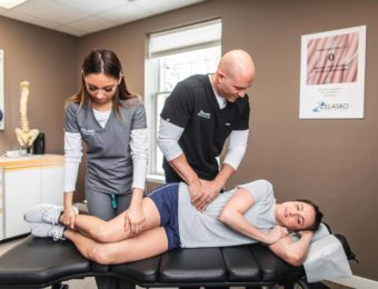 Chiropractor Dr. Brian A. Zelasko And His Assistant Treating Female Patient's Side While She Lays Down On Treatment Table
