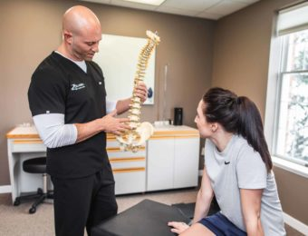 Chiropractor Dr. Brian A. Zelasko In Examination Room Showing Female Patient A Model Of A Spine