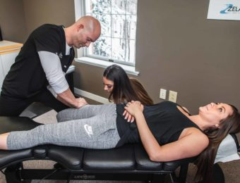 Chiropractor Dr. Brian A. Zelasko With Assistant Treating Female Patient's Thigh At Prime Spine Associates