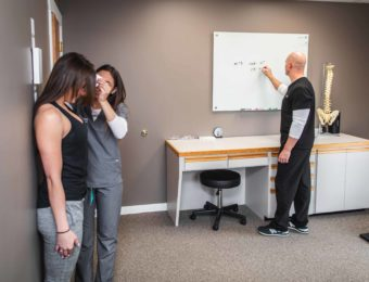 Chiropractic Assistant Measuring Female Patient's Flexibility While Dr. Zelasko Takes Notes On Whiteboard In Examination Room