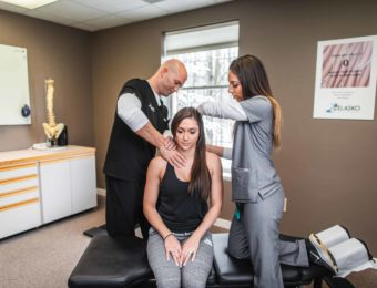 Chiropractor Dr. Brian A. Zelasko And His Assistant Treating Sitting Female Patient's Shoulder At Prime Spine Associates