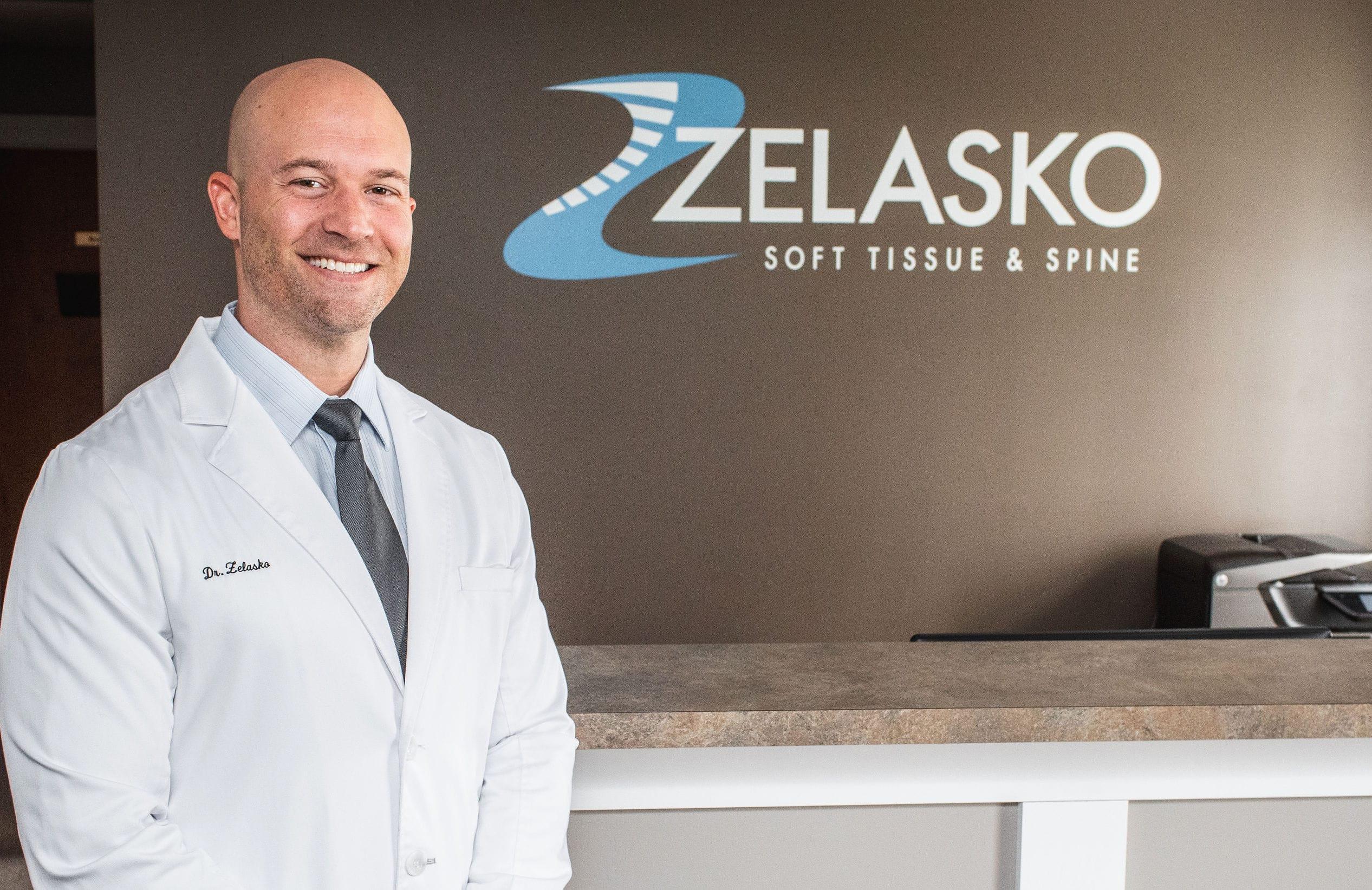 Chiropractor Dr. Brian A. Zelasko standing in white physician's lab coat in front of Zelasko Soft Tissue & Spine Logo within practice