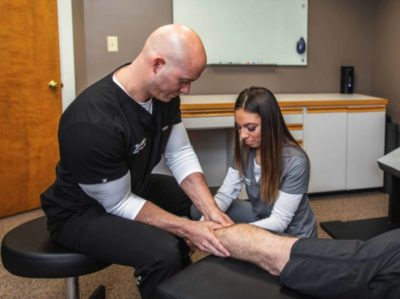 Chiropractor Dr. Brian A. Zelasko Of Prime Spine Associates Treating A Male Patient's Ankle On Treatment Table