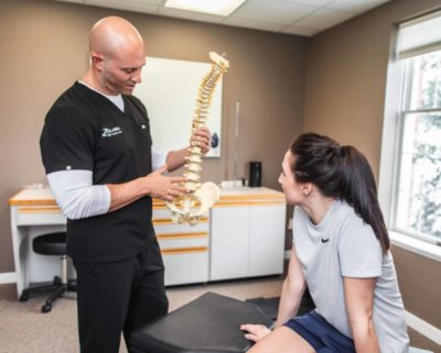 Dr. Brian A. Zelasko Of Prime Spine Associates Explaining An Injury To A Female Patient Using A Model Of A Spine