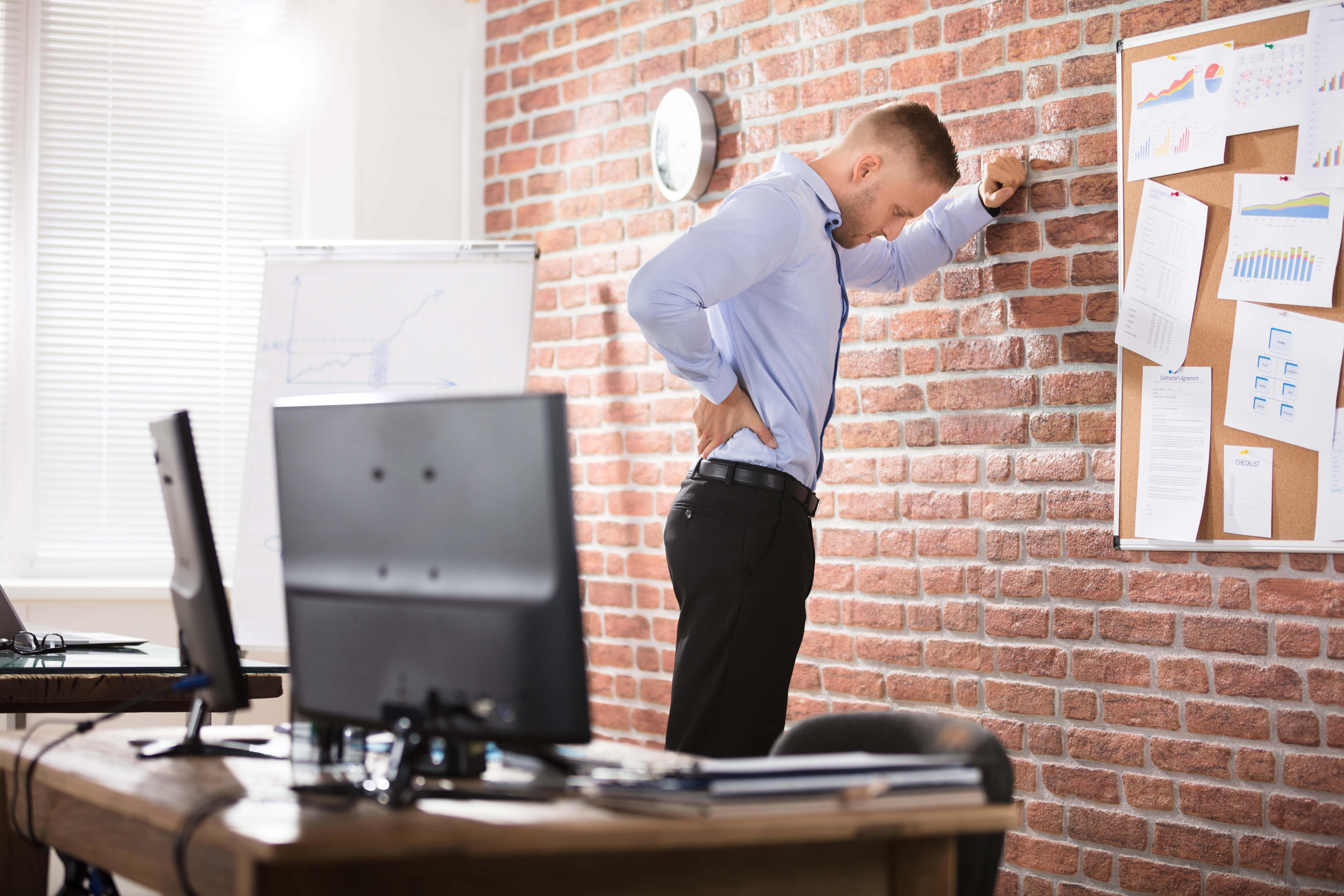 Businessman Leaning Against The Brick Wall Having Back Pain In Office