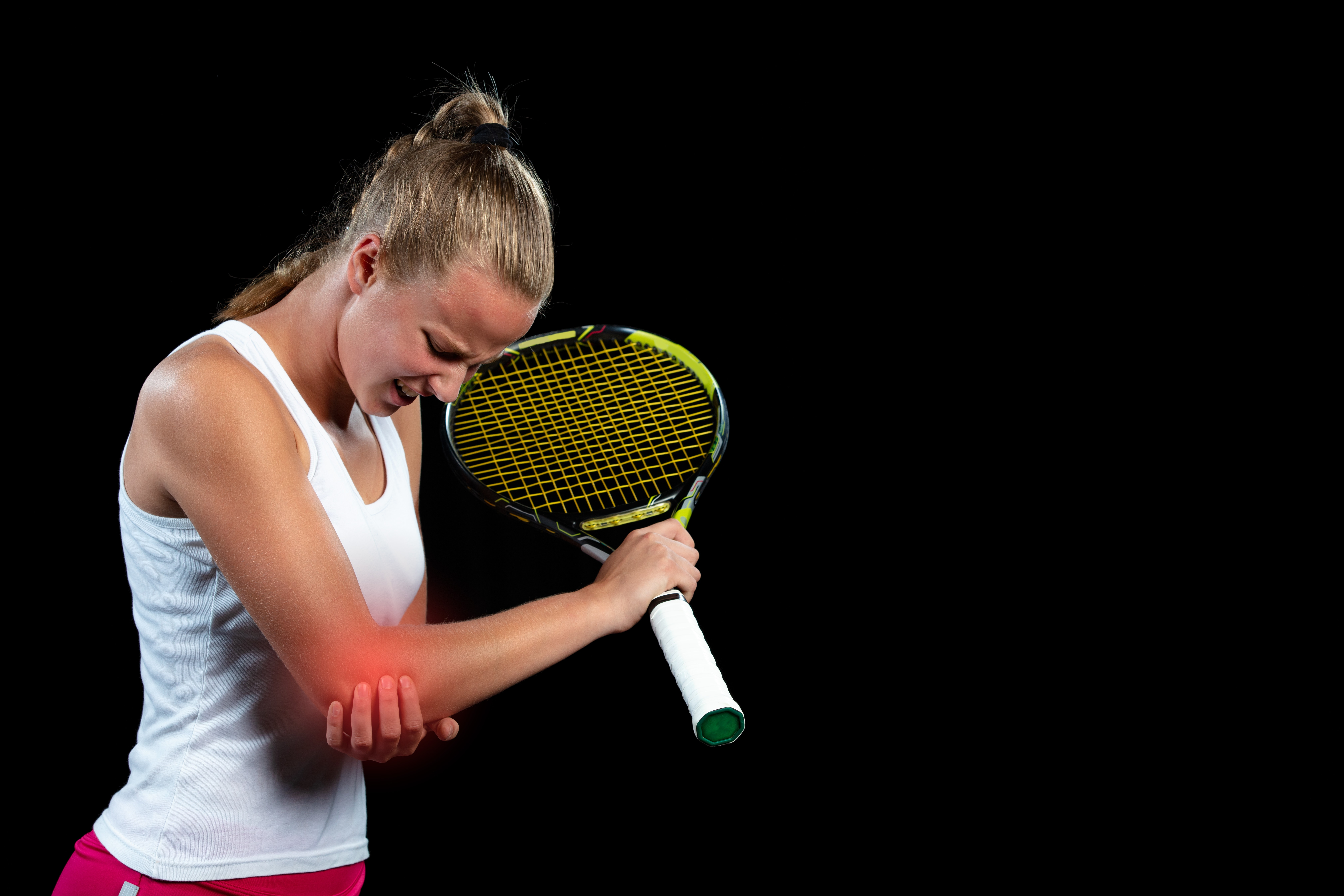 female tennis player holding painful elbow
