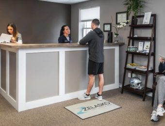 Clean Waiting Room With Patients And Staff At Prime Spine Associates